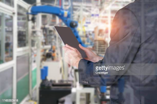businessman hand using tablet check productivity , heavy automation robot arm machine in smart factory industrial 4.0. - deep learning stock pictures, royalty-free photos & images