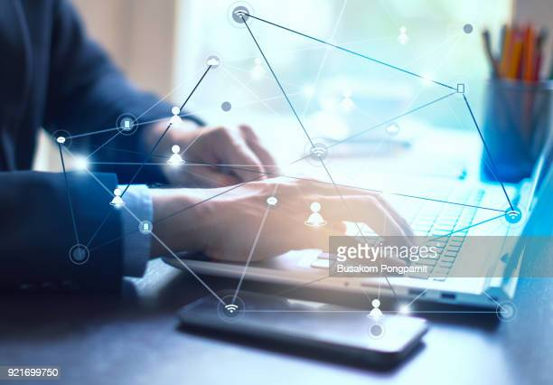 Businessman hand working on laptop computer on wooden desk as concept and technology social media network diagram