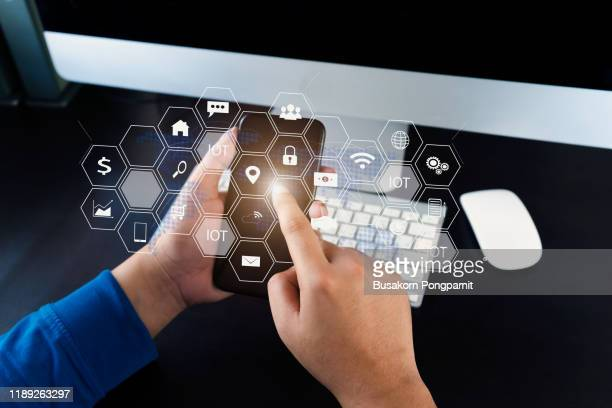 businessman hand working with mobile phone and laptop computer with technology digital graphic - customer engagement stock pictures, royalty-free photos & images