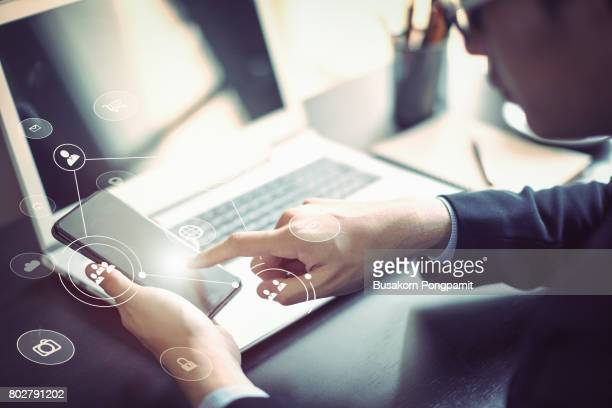 businessman hand working with mobile phone and laptop computer  with technology digital graphic - marketing icons stock photos and pictures