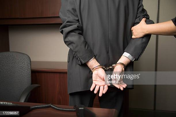 Businessman handcuffed and being lead away