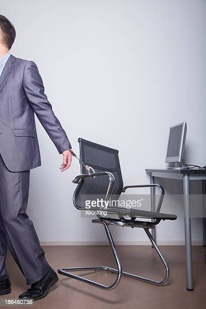 Businessman handcuffed to his office chair, walking away