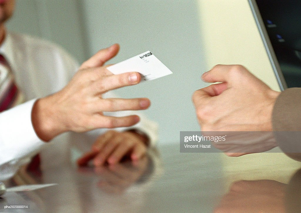Businessman handing business card to man. : Stockfoto