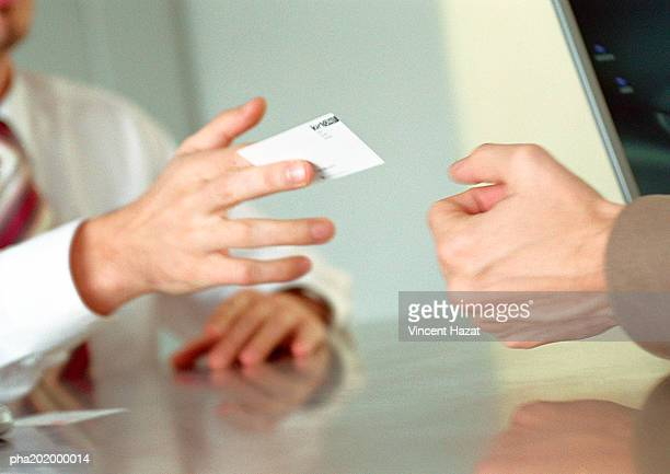 Businessman handing business card to man.