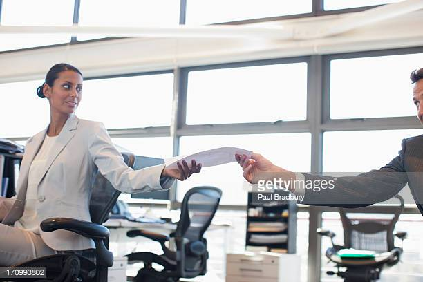 businessman handing co-worker paperwork in office - doing a favor stock pictures, royalty-free photos & images