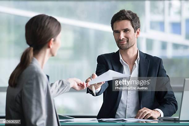 Businessman handing document to client