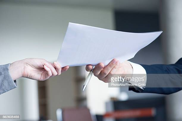 Businessman handing document to colleague, cropped