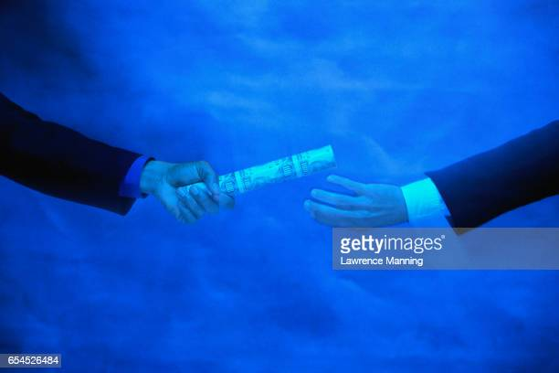 Businessman Handing off Baton Made of Money