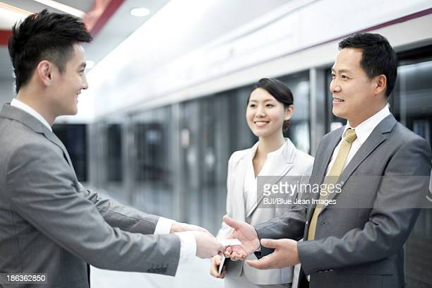 Businessman handing over business card to new friends on subway platform