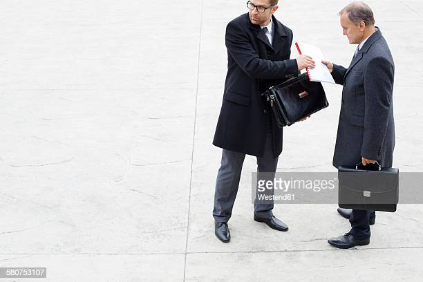 businessman handing over documents to partner secretly - corruption stock pictures, royalty-free photos & images