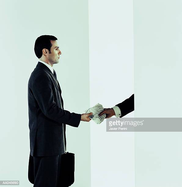 businessman handing over stack of bills - canadian one hundred dollar bill stock pictures, royalty-free photos & images