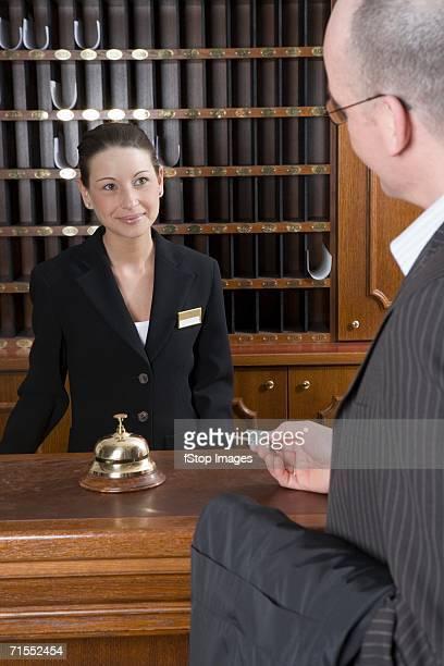 Businessman handing room key to hotel clerk