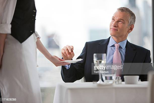 Businessman handing waitress credit card in restaurant