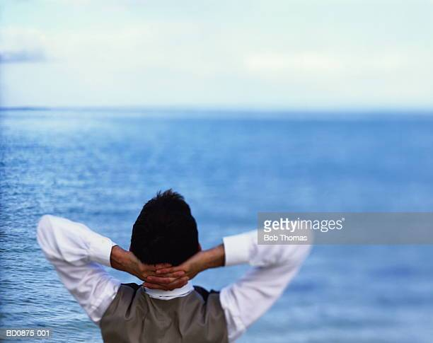 Businessman, hands clasped behind head, sea in background, rear view
