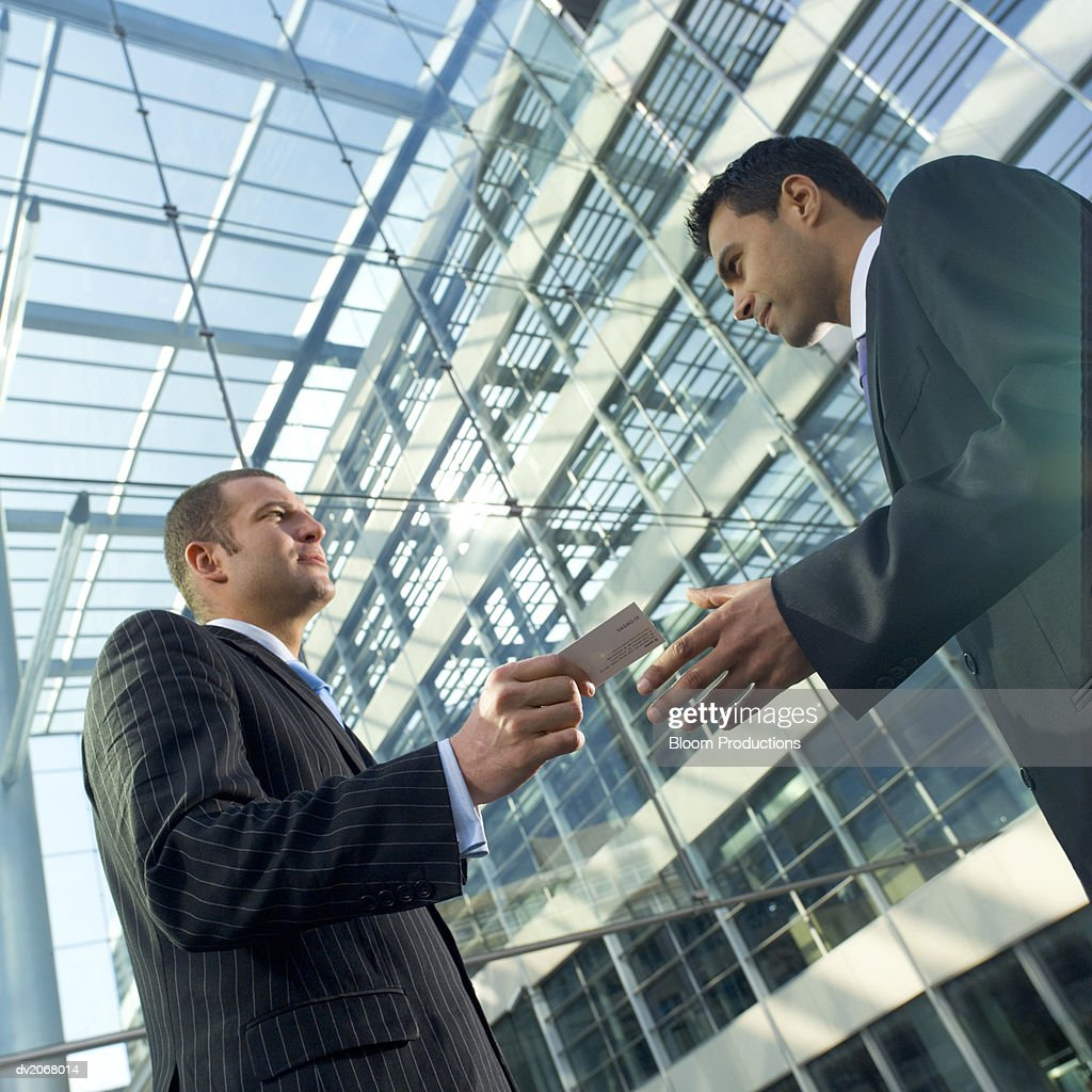 Businessman Hands His Business Card to a Colleague : Stock Photo