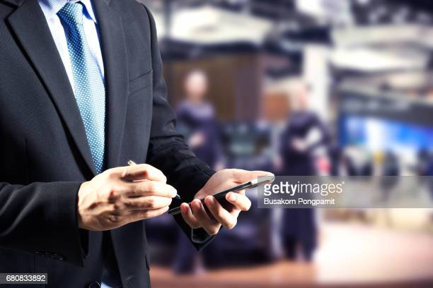 Businessman hands holding trade booking using smart phone with blurred background of new car displayed in showroom dealer, buying new car