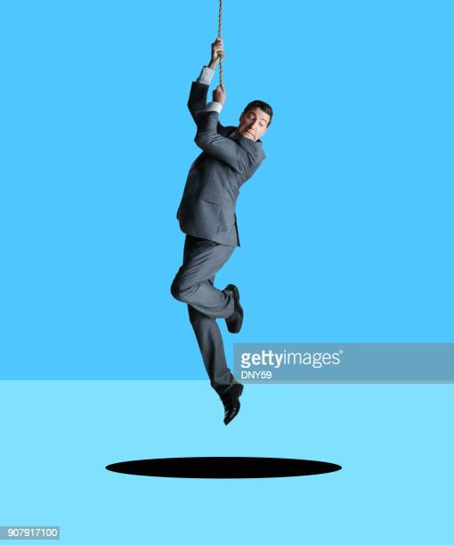 Businessman Hanging From Rope Looks Down At Hole