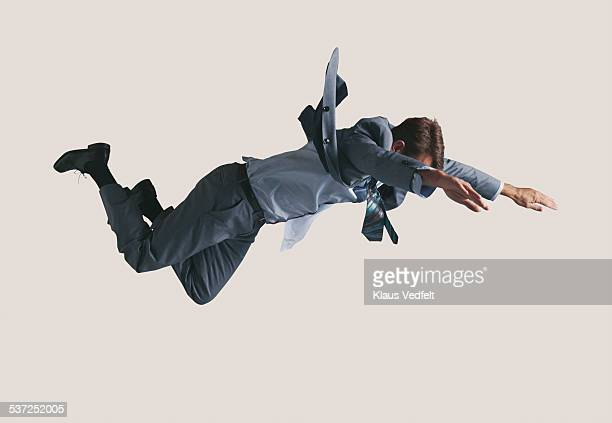 businessman hanging in the air, wearing grey suit - fliegen stock-fotos und bilder