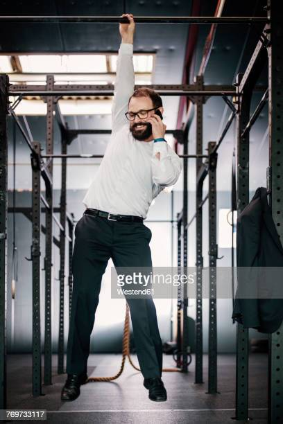 businessman hanging on bar and talking on the phone - hanging stock photos and pictures