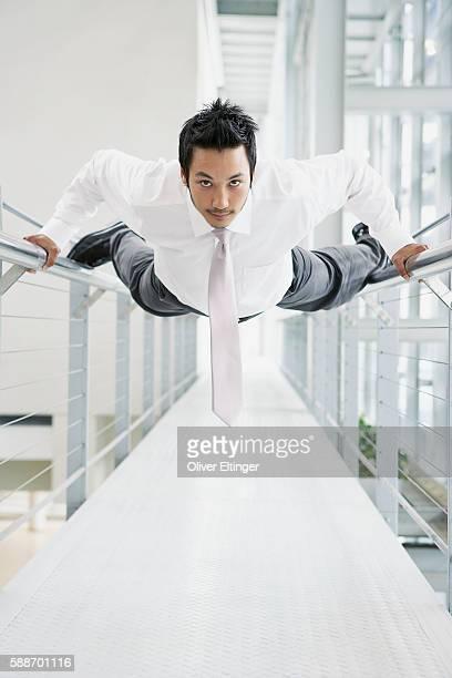 businessman hanging on railings - oliver eltinger stock-fotos und bilder