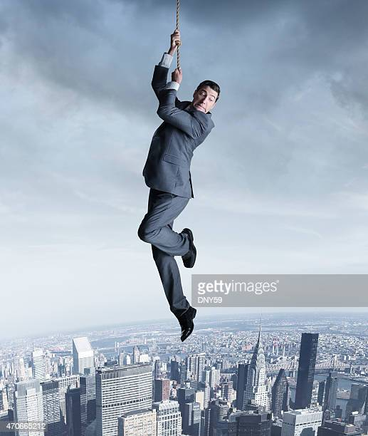 Businessman hanging on to a rope above city
