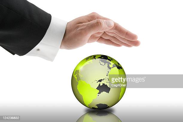 A businessman has his hand over a globe