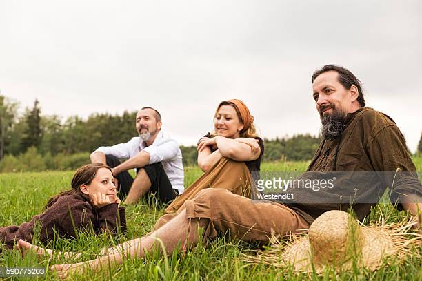 Businessman having a break on the countryside with three villagers