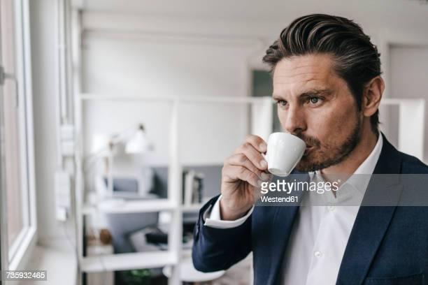 businessman having a coffee at the window - caffè bevanda foto e immagini stock