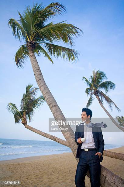 Businessman having a coffee on the beach