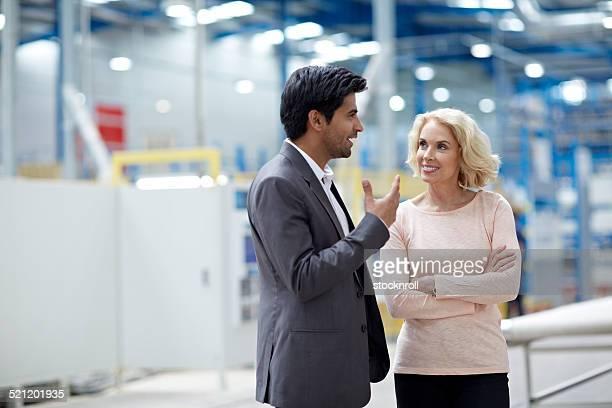 Geschäftsmann, ein Gespräch mit senior weiblichen Kollegen in Fabrik