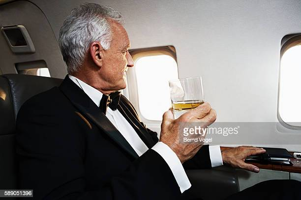 Businessman having a drink on a plane