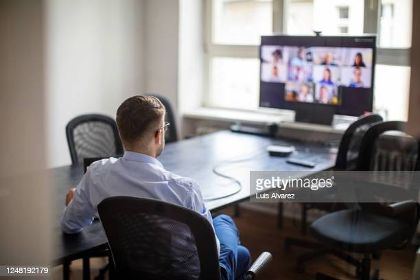 businessman having a meeting with his team over a video call - employee stock pictures, royalty-free photos & images
