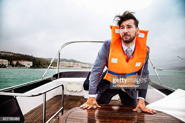 Businessman having a panic attack on his yacht in storm
