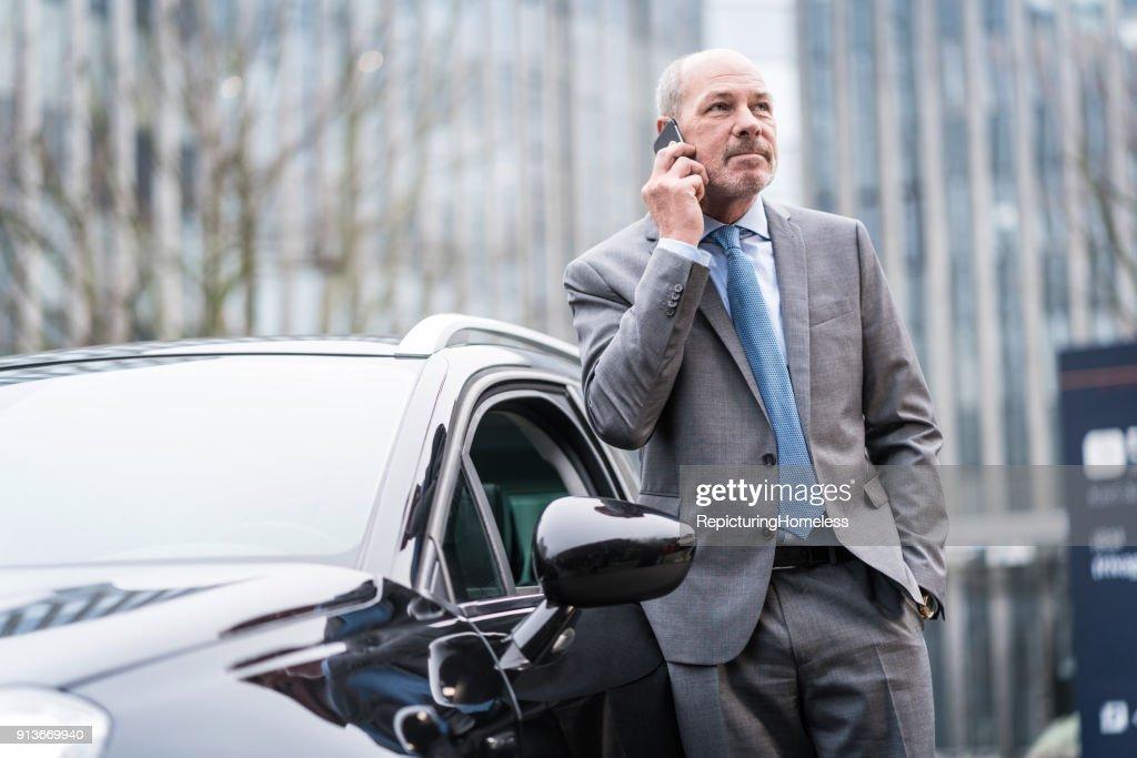 Ein Geschäftsmann lehnt sich an ein Auto und führt ein Telefonat : Stock-Foto