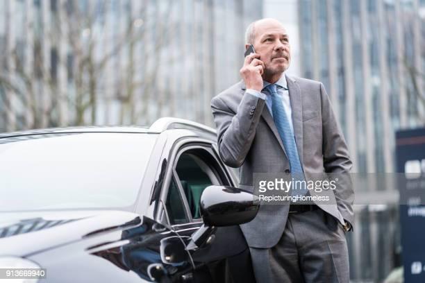 Ein Geschäftsmann lehnt sich an ein Auto und führt ein Telefonat