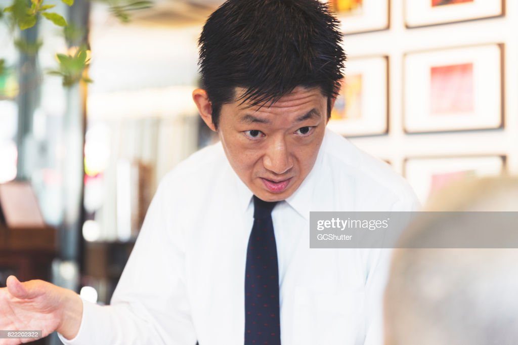Businessman having a stern conversation with a colleague : Stock Photo