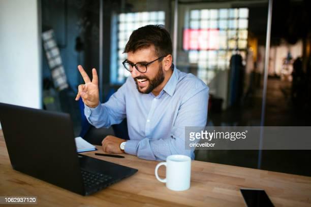 zakenman met een video-oproep op kantoor - voip stockfoto's en -beelden