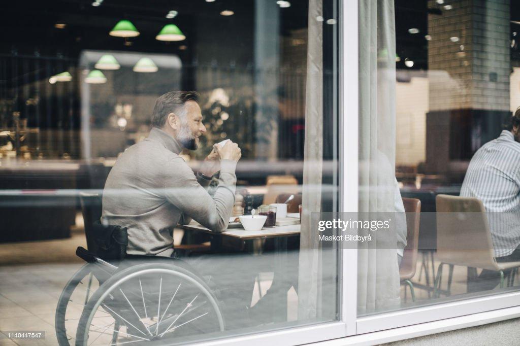 Businessman having breakfast with businesswoman at table in restaurant seen through window glass : Stockfoto
