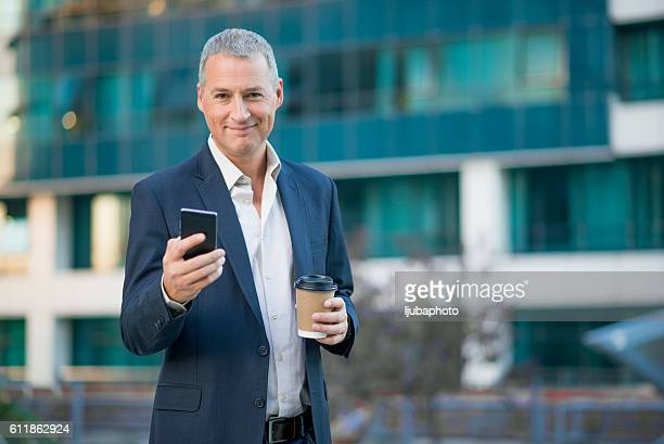 businessman having coffee break holding coffee to go outside