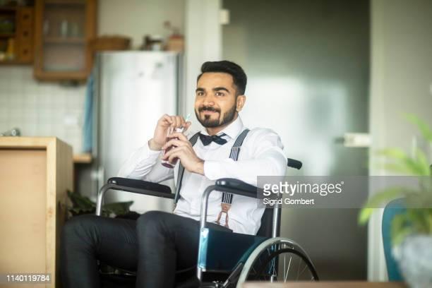 businessman having drink in wheelchair - sigrid gombert stock-fotos und bilder