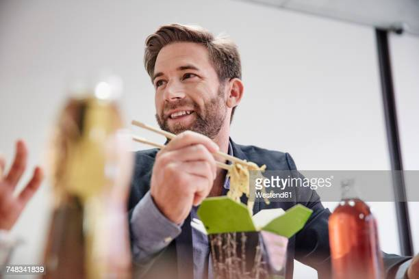 Businessman having lunch break with asian food