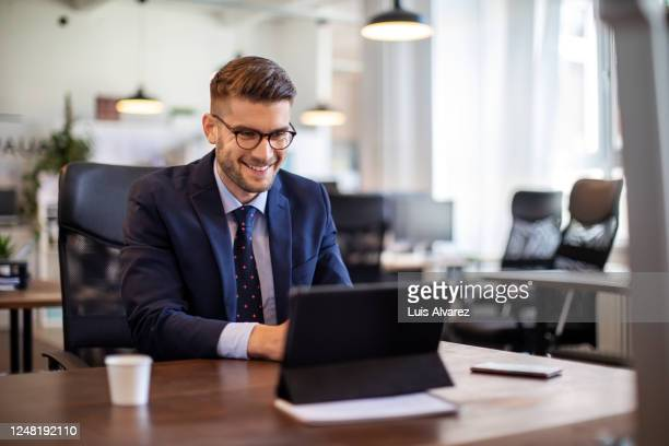 businessman having online briefing with team at office - one mid adult man only stock pictures, royalty-free photos & images