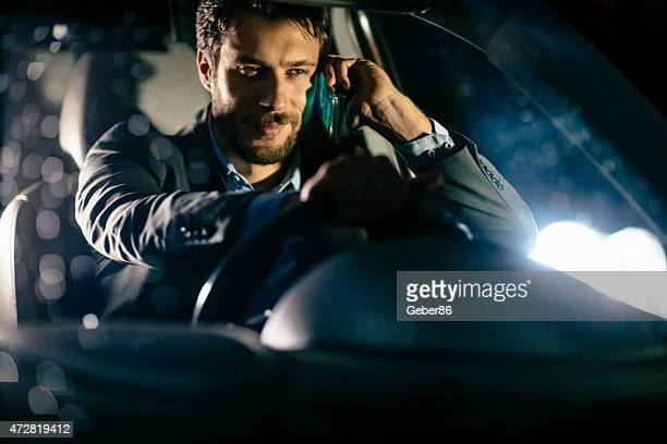 Businessman having phone call in his car