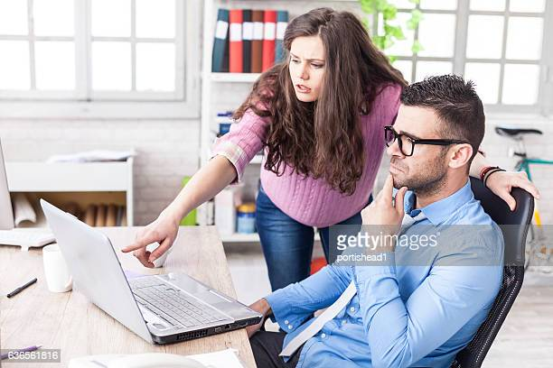 Businessman having problem on laptop at workplace