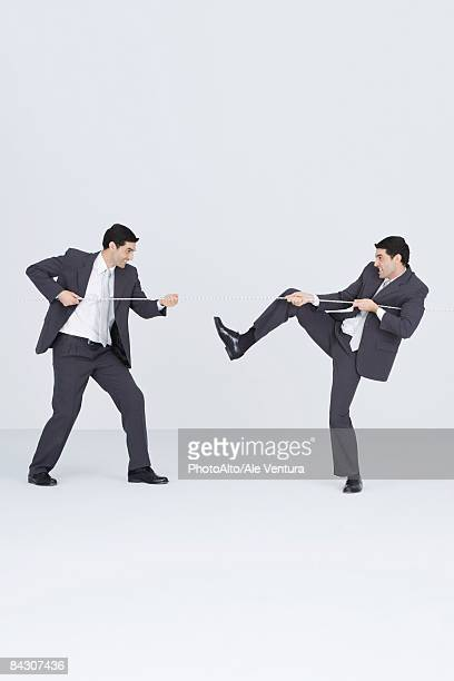 Businessman having tug-of-war with self