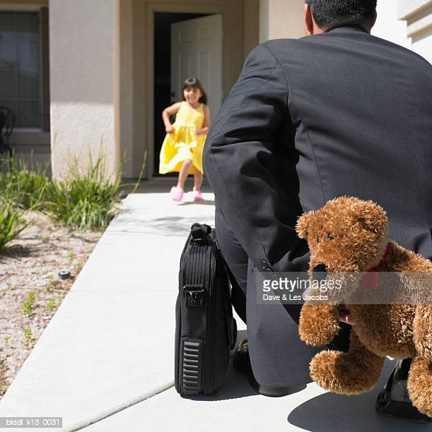 Businessman hiding a teddy bear behind his back