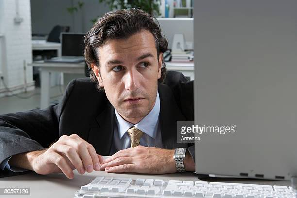 A businessman hiding behind a computer