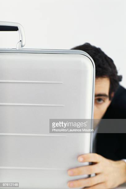 Businessman hiding behind briefcase
