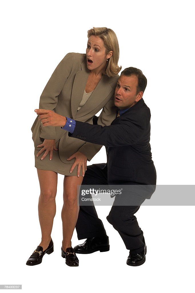 Businessman hiding behind woman and pointing : Stockfoto