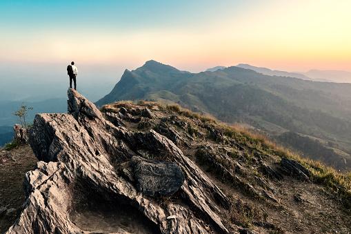 businessman hike on the peak of rocks mountain at sunset 512151814